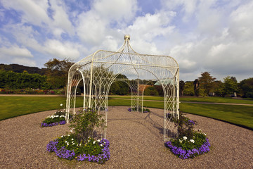 Wrought iron arbour in a landscaped park.
