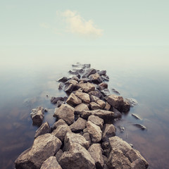 Minimalist misty seascape with rocks at long exposure.