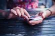 Leinwanddruck Bild - Woman using her smart phone outside