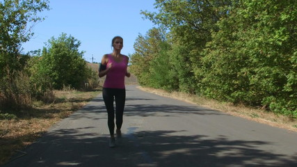 Fitness athletic girl jogging along the road