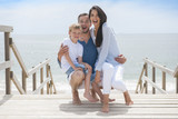 happy family  standing on a wood pontoon in front of the sea in