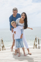 happy family of three persons in front of the sea