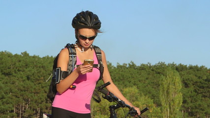 Young woman cyclist on her mountain bike using smart phone