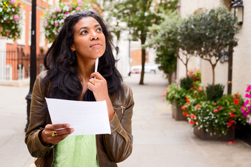 thoughtful woman holding a letter.