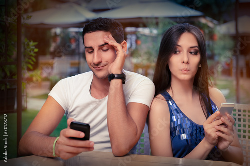 Secretive Couple with Smart Phones in Their Hands - 70178712