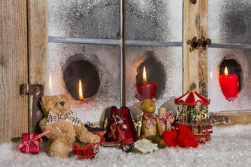 Weihnachtlich dekoriertes Fenster mit alten Spielsachen