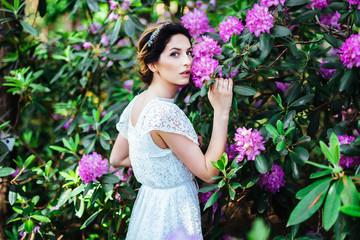 fashion beautiful girl in a flowers garden