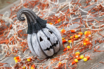 Angled scary black and white Halloween pumpkin on rustic wood