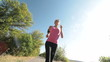 Fit female runner running on countryside road