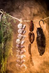 Ham, sausage and garlic in a homemade smokehouse