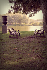 Two benches in the park on a background of lake