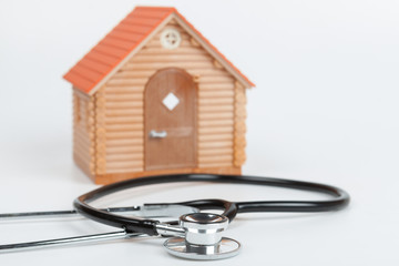 Stethoscope and Model House on white background