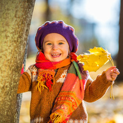Happy little girl playing in the autumn park