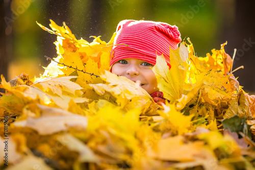 Leinwanddruck Bild Little girl playing with autumn leaves