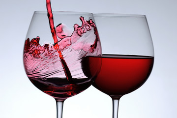 Pouring red wine in two wine glasses