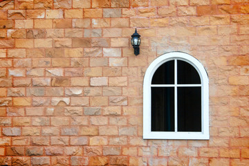 window and lamp on the brick wall