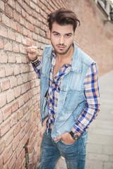 man posing for the camera near a brick wall