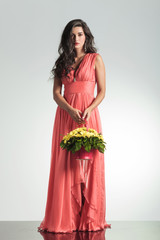 fashion young woman in elegant red dress holding  flower basket