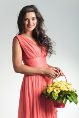 sexy young woman with flower basket is laughing