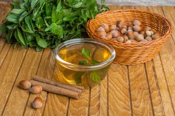 Mint, cinnamon, hazelnut and tea on  wooden background.