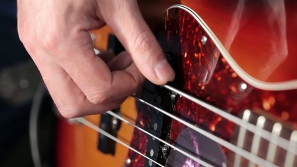 Playing at bass instrument close up footage