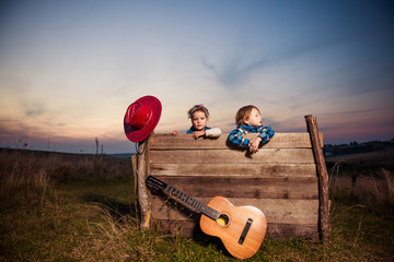 kids and guitar at old wooden meadow construction