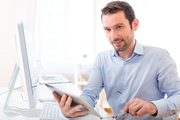 Young attractive man with tablet at the office