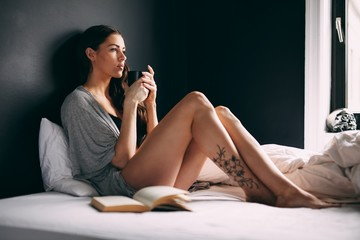 Thoughtful woman with her coffee mug on bed