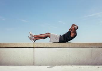 Athlete doing sit-ups against sky.