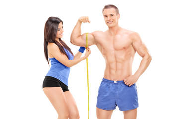 Girl measuring a bicep of a young male athlete