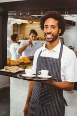 Handsome waiter smiling at camera holding tray