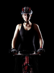 low key silhouette of a girl cyclist   on black background