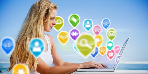 Composite image of pretty blonde using her laptop at the beach