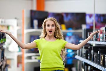 Красивая девушка в магазине телевизоров и электротехники