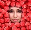 Woman beauty face with raspberry frame, close-up