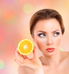 Beautiful young woman with bright make-up, holding orange,