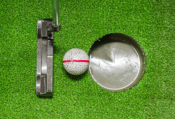 Old golf balls and putter on artificial grass for practice.
