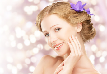 Beauty face  of healthy girl with purple and lilac flowers