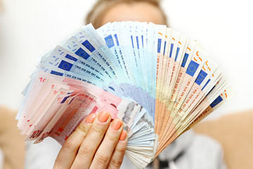 woman holds euro money banknotes in front