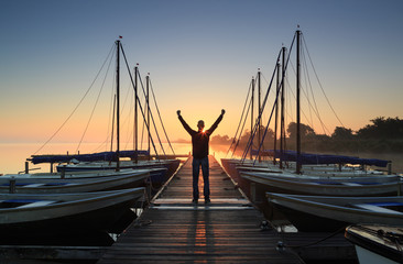 Man cheering on a jetty in a marina during a foggy sunrise.