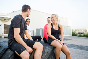 Friends Relaxing On Tire After Workout
