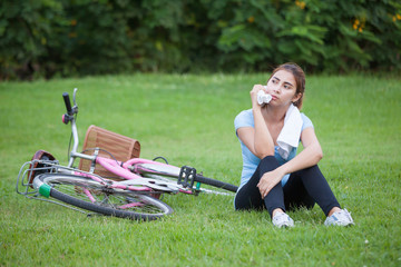Happy Young Woman riding bicycle outside