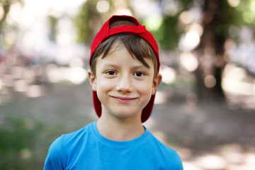 Little boy in cap outdoor look into camera