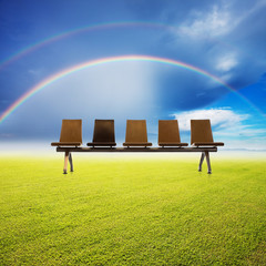 chairs over the grass filed and rainbow background