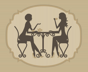Silhouette of two beautiful girls talking in a cafe