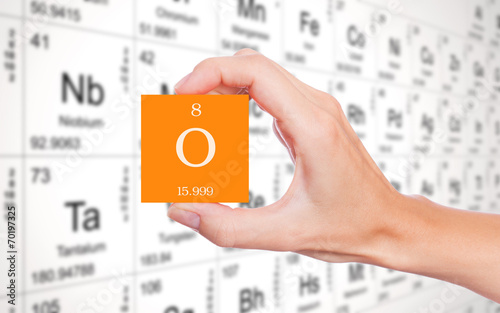 Oxygen symbol handheld in front of the periodic table - 70197325