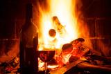 Kaminfeuer mit Weinflasche und Weinglas