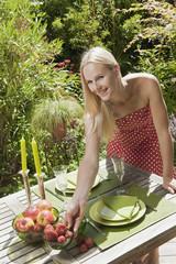 Österreich, Frau, Obstschale auf dem Tisch im Garten