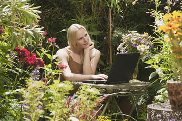 Österreich, Frau sitzt am Tisch im Garten mit Laptop
