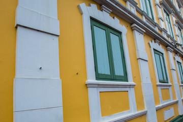 Green wooden windows on the yellow wall